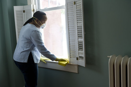 woman wearing mask and gloves cleaning inside her house
